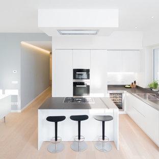 Ispirazione per una grande cucina minimal con lavello a vasca singola, ante lisce, ante bianche, pavimento in legno massello medio e isola