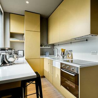 Foto di una cucina ad U design con ante grigie, elettrodomestici in acciaio inossidabile e top bianco