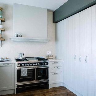 Foto di una cucina a L tradizionale con ante con riquadro incassato, ante grigie, paraspruzzi grigio, elettrodomestici neri, pavimento in legno massello medio e nessuna isola