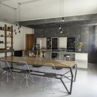 Esempio di una grande cucina abitabile industriale con top in quarzo composito, elettrodomestici in acciaio inossidabile, pavimento in gres porcellanato, isola, pavimento grigio, top nero, ante lisce e ante con finitura invecchiata