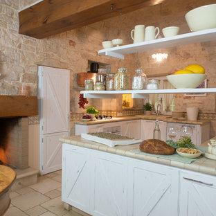 Immagine di una cucina country con paraspruzzi beige, elettrodomestici da incasso, penisola, pavimento beige, ante con bugna sagomata, ante con finitura invecchiata, top piastrellato e pavimento in terracotta