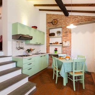 Foto di una piccola cucina country con ante lisce, ante verdi e pavimento in terracotta