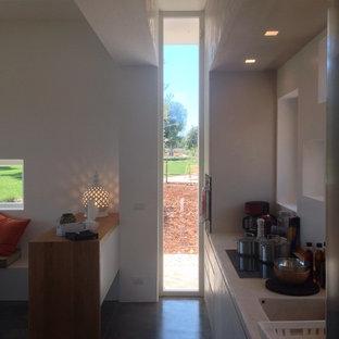 他の地域の巨大なモダンスタイルのおしゃれなキッチン (一体型シンク、インセット扉のキャビネット、コンクリートカウンター、ベージュキッチンパネル、ガラスまたは窓のキッチンパネル、コンクリートの床、グレーの床、ベージュのキッチンカウンター) の写真