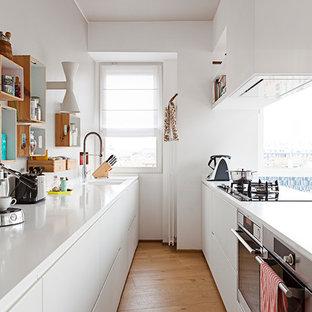 Immagine di una grande cucina minimal con ante lisce, ante bianche, top in quarzo composito, paraspruzzi bianco, elettrodomestici in acciaio inossidabile, pavimento in legno massello medio, penisola, pavimento marrone e lavello sottopiano