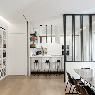 Esempio di una cucina ad U contemporanea con ante lisce, ante bianche, elettrodomestici in acciaio inossidabile, parquet chiaro, penisola, pavimento beige e top bianco