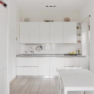 Ispirazione per una cucina abitabile minimal di medie dimensioni con ante lisce, ante bianche, paraspruzzi bianco, nessuna isola, lavello a doppia vasca, paraspruzzi con lastra di vetro e parquet chiaro