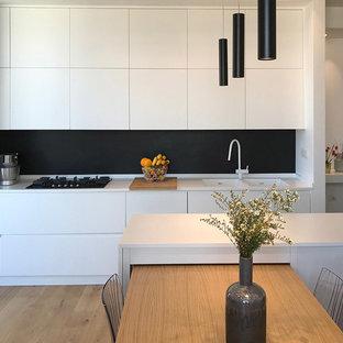 Foto di una cucina contemporanea di medie dimensioni con ante lisce, ante bianche, paraspruzzi nero, lavello a doppia vasca, parquet chiaro, top in superficie solida, elettrodomestici in acciaio inossidabile, isola e top bianco