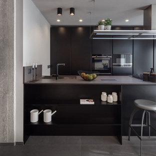 Esempio di una cucina parallela industriale di medie dimensioni con lavello sottopiano, ante lisce, ante nere, top in quarzo composito, elettrodomestici neri, pavimento in gres porcellanato, pavimento grigio, top grigio e penisola
