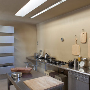 Photo of a large contemporary open plan kitchen in Turin with an integrated sink, flat-panel cabinets, stainless steel cabinets, stainless steel benchtops, stainless steel appliances, concrete floors, no island, beige floor and beige benchtop.