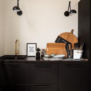 他の地域の小さい北欧スタイルのおしゃれなキッチン (ドロップインシンク、フラットパネル扉のキャビネット、黒いキャビネット、木材カウンター、白いキッチンパネル、セメントタイルの床、アイランドなし、赤い床、茶色いキッチンカウンター) の写真