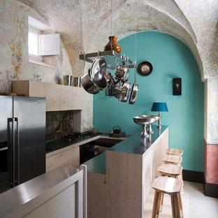 Ispirazione per una cucina ad U mediterranea con ante lisce, ante in legno chiaro, top in acciaio inossidabile, paraspruzzi multicolore, elettrodomestici in acciaio inossidabile e penisola