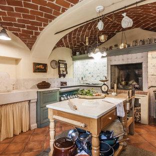 Immagine di una cucina a L chic con isola, lavello integrato, paraspruzzi bianco, pavimento in terracotta, pavimento marrone e top bianco