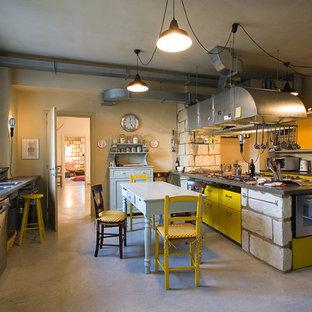 Bild på ett stort industriellt linjärt kök och matrum, med släta luckor, gula skåp, rostfria vitvaror, betonggolv, en halv köksö, en dubbel diskho och bänkskiva i rostfritt stål