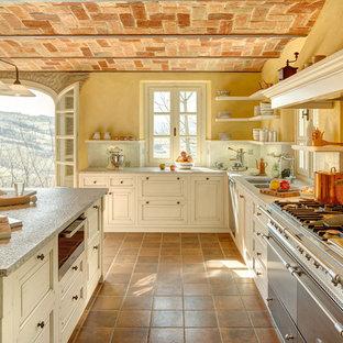 Bild på ett stort lantligt l-kök, med granitbänkskiva, rostfria vitvaror, klinkergolv i terrakotta, en köksö, en dubbel diskho, beige skåp, flerfärgad stänkskydd och orange golv