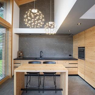 Immagine di una cucina minimal con lavello sottopiano, ante lisce, ante in legno scuro, paraspruzzi grigio, elettrodomestici da incasso, isola, pavimento grigio e top nero