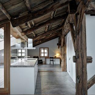 Immagine di una grande cucina rustica con ante lisce, ante bianche, pavimento in cemento, pavimento grigio, lavello sottopiano, paraspruzzi a finestra e top grigio