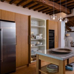Ispirazione per una cucina mediterranea con ante lisce, ante in legno scuro, elettrodomestici in acciaio inossidabile, isola, pavimento marrone e top grigio