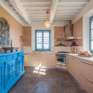 This is an example of a mid-sized mediterranean l-shaped kitchen in Florence with flat-panel cabinets, concrete floors, no island, grey floor, beige benchtop, a double-bowl sink, light wood cabinets, beige splashback and stainless steel appliances.