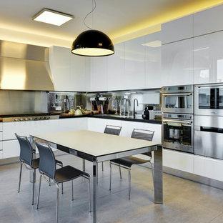 Immagine di una cucina minimal di medie dimensioni con lavello da incasso, ante lisce, ante in acciaio inossidabile, paraspruzzi a effetto metallico, paraspruzzi con piastrelle di metallo, elettrodomestici in acciaio inossidabile e pavimento grigio