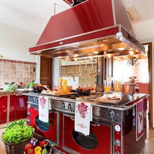 Idee per una cucina chic con ante lisce, ante rosse, paraspruzzi beige, elettrodomestici colorati, isola e pavimento beige