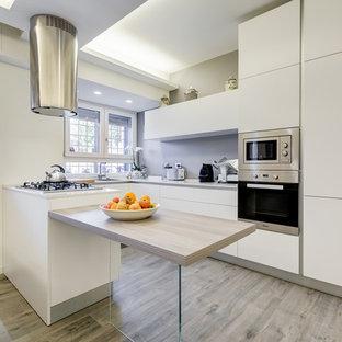 Modelo de cocina comedor en U, minimalista, de tamaño medio, con fregadero integrado, armarios con paneles lisos, salpicadero verde, electrodomésticos de acero inoxidable, suelo laminado, península y suelo gris