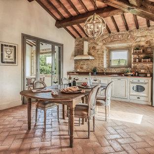 На фото: линейная кухня среднего размера в средиземноморском стиле с обеденным столом, врезной раковиной, фасадами с утопленной филенкой, белыми фасадами, коричневым фартуком, фартуком из каменной плитки, белой техникой, полом из терракотовой плитки, коричневым полом, коричневой столешницей и деревянным потолком без острова с