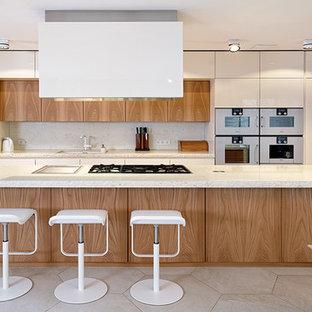 Esempio di una grande cucina minimal con isola, lavello da incasso, ante lisce, ante in legno chiaro e elettrodomestici bianchi
