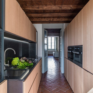 Photo of a mid-sized contemporary galley kitchen in Milan with flat-panel cabinets, black splashback, terra-cotta floors, no island, an undermount sink, light wood cabinets and brown floor.