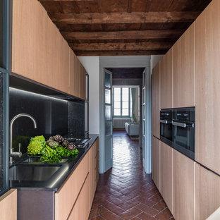 Esempio di una cucina parallela contemporanea di medie dimensioni con ante lisce, paraspruzzi nero, pavimento in terracotta, nessuna isola, lavello sottopiano, ante in legno chiaro e pavimento marrone
