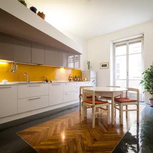Пример оригинального дизайна: большая линейная кухня в современном стиле с обеденным столом, врезной раковиной, плоскими фасадами, белыми фасадами, желтым фартуком и полом из керамогранита