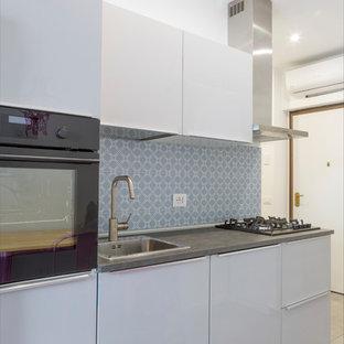 Foto di una piccola cucina lineare contemporanea con ante lisce, ante bianche, paraspruzzi blu, elettrodomestici neri e top grigio