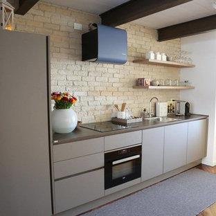 Foto på ett funkis linjärt kök, med en enkel diskho, släta luckor, grå skåp, stänkskydd i tegel, svarta vitvaror och mörkt trägolv