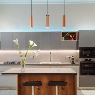 Idee per una cucina parallela design con lavello da incasso, ante lisce, ante grigie, elettrodomestici neri, isola, pavimento bianco e top grigio