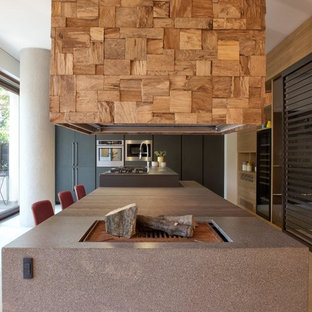 Esempio di un'ampia cucina parallela minimal con isola, top nero, pavimento in gres porcellanato, ante lisce, ante nere e pavimento beige