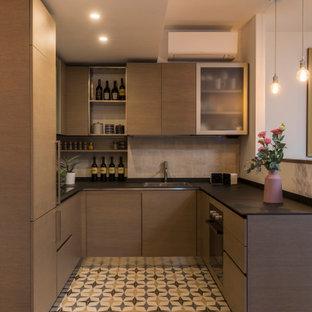Foto di una piccola cucina ad U design con lavello a doppia vasca, ante lisce, ante in legno scuro, paraspruzzi beige, pavimento in gres porcellanato, nessuna isola, pavimento multicolore e top nero