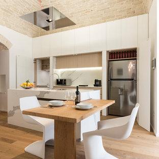 Exempel på ett stort medelhavsstil vit vitt kök, med släta luckor, vita skåp, vitt stänkskydd, rostfria vitvaror, mellanmörkt trägolv, brunt golv, en undermonterad diskho och en köksö
