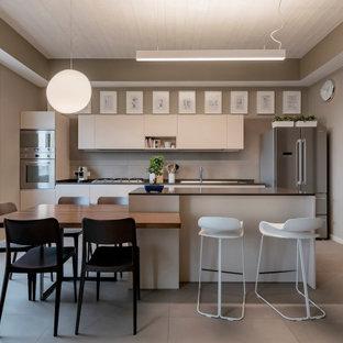Idee per una cucina parallela contemporanea con ante lisce, ante in legno chiaro, elettrodomestici in acciaio inossidabile, pavimento in cemento, isola, pavimento grigio, top nero e soffitto in legno