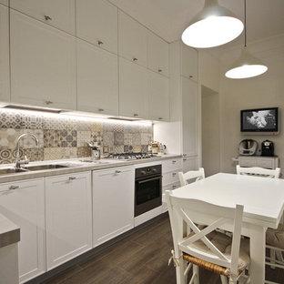 他の地域の中サイズのカントリー風おしゃれなキッチン (ドロップインシンク、落し込みパネル扉のキャビネット、白いキャビネット、珪岩カウンター、マルチカラーのキッチンパネル、セラミックタイルのキッチンパネル、黒い調理設備、磁器タイルの床、アイランドなし、グレーの床、ピンクのキッチンカウンター) の写真