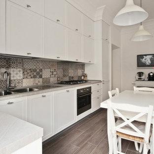 他の地域の中サイズのカントリー風おしゃれなキッチン (落し込みパネル扉のキャビネット、白いキャビネット、マルチカラーのキッチンパネル、セラミックタイルのキッチンパネル、磁器タイルの床、アイランドなし、グレーの床、ドロップインシンク、珪岩カウンター、黒い調理設備、ピンクのキッチンカウンター) の写真