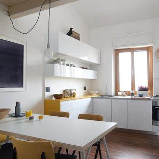 Foto di una cucina scandinava di medie dimensioni con ante lisce, ante bianche, elettrodomestici in acciaio inossidabile, pavimento in legno massello medio e top giallo