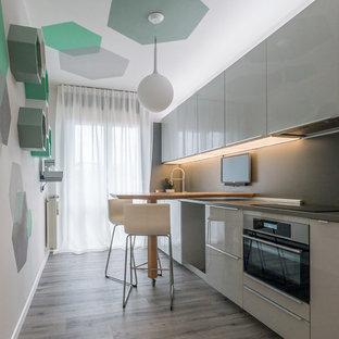 Cette image montre une petite cuisine ouverte linéaire design avec un évier 1 bac, un placard à porte plane, des portes de placard grises, un plan de travail en stratifié, une crédence grise, un électroménager en acier inoxydable, un sol en linoléum, une péninsule, un sol gris et un plan de travail gris.