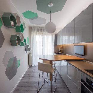 Удачное сочетание для дизайна помещения: маленькая линейная кухня-гостиная в современном стиле с одинарной раковиной, плоскими фасадами, серыми фасадами, столешницей из ламината, серым фартуком, техникой из нержавеющей стали, полом из линолеума, полуостровом, серым полом и серой столешницей - самое интересное для вас