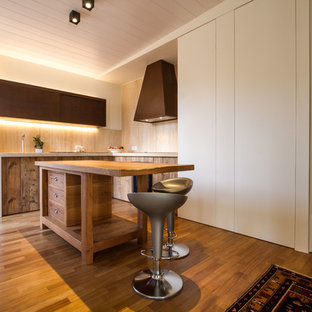 Immagine di una cucina a L mediterranea con ante lisce, ante in legno scuro, paraspruzzi beige, paraspruzzi in legno, pavimento in legno massello medio, un'isola e pavimento marrone
