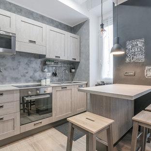 Ispirazione per una cucina design di medie dimensioni con lavello da incasso, ante con riquadro incassato, ante in legno chiaro, top in superficie solida, paraspruzzi grigio, elettrodomestici in acciaio inossidabile e parquet chiaro