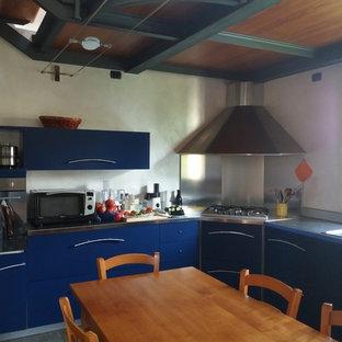 他の地域の広いコンテンポラリースタイルのおしゃれなキッチン (ドロップインシンク、フラットパネル扉のキャビネット、青いキャビネット、ステンレスカウンター、グレーのキッチンパネル、パネルと同色の調理設備、ライムストーンの床、アイランドなし、黄色い床、グレーのキッチンカウンター) の写真