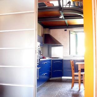 他の地域の大きいコンテンポラリースタイルのおしゃれなキッチン (ドロップインシンク、フラットパネル扉のキャビネット、青いキャビネット、ステンレスカウンター、グレーのキッチンパネル、パネルと同色の調理設備、ライムストーンの床、アイランドなし、黄色い床、グレーのキッチンカウンター) の写真