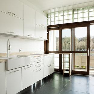 Idee per una cucina lineare minimal di medie dimensioni con pavimento in gres porcellanato, lavello stile country, ante lisce, ante bianche, top in legno, pavimento nero e top marrone