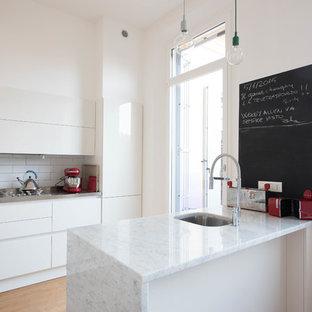Idee per una cucina contemporanea con lavello sottopiano, ante lisce, ante bianche, paraspruzzi bianco, paraspruzzi con piastrelle diamantate, parquet chiaro, penisola, pavimento beige e top bianco