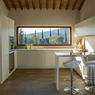 Foto di una cucina in campagna di medie dimensioni con lavello da incasso, ante lisce, ante bianche e parquet scuro
