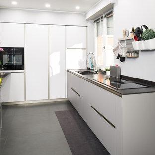 Immagine di una cucina a L design di medie dimensioni e chiusa con pavimento grigio, lavello da incasso, ante lisce, ante grigie, top in superficie solida, elettrodomestici neri, pavimento in gres porcellanato e top nero